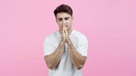 Photo pour Homme contrarié montrant les mains priantes isolées sur rose - image libre de droit