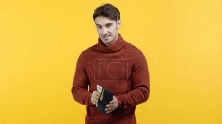 Wesoły człowiek trzyma portfel i dolary odizolowane na żółto