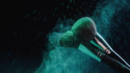 cepillos cosméticos haciendo salpicadura de pintura holi azul cerca de polvo cayendo sobre negro