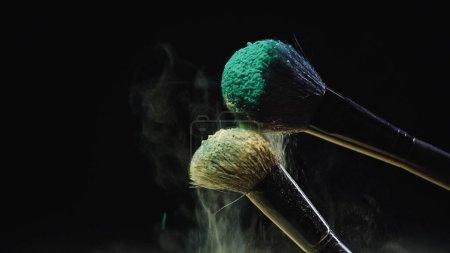 cepillos cosméticos con polvo azul y amarillo sobre negro