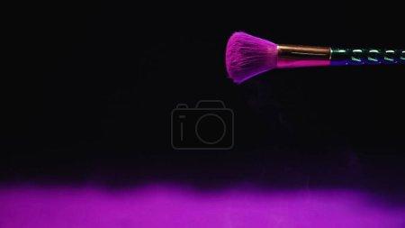 Photo pour Pinceau cosmétique avec peinture holi violet sur fond noir - image libre de droit