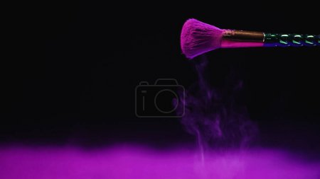 Kosmetikpinsel mit lila Puder auf schwarzem Hintergrund