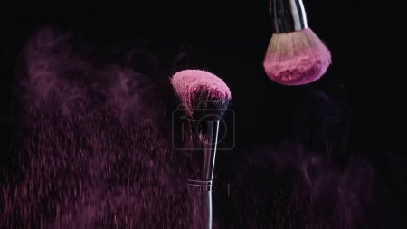 Photo for Cosmetic brushes with pink powder falling down on black - Royalty Free Image