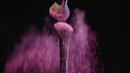 cosmetic brushes with pink holi powder falling down on black