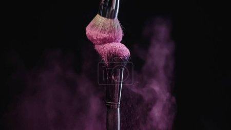 pinceaux cosmétiques doux avec poudre holi rose près de la poussière de couleur sur noir