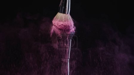 Photo for Cosmetic brushes hitting and making splashes of colorful purple holi paint on black background - Royalty Free Image