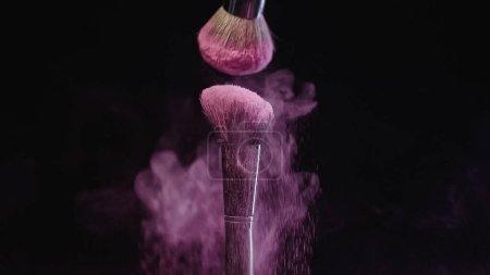 Photo for Soft cosmetic brushes making splashes of pink holi paint on black background - Royalty Free Image