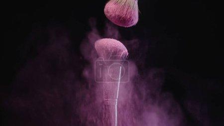 Photo pour Pinceaux cosmétiques doux près des éclaboussures de poussière rose sur fond noir - image libre de droit