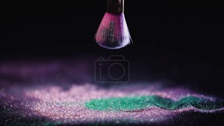cosmetic brush above shiny pink and turquoise dust on black background