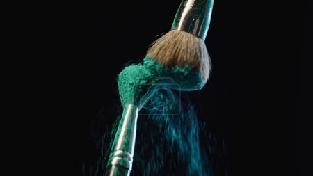 Photo for Cosmetic brushes hitting and making splashes of blue holi paint on black background - Royalty Free Image