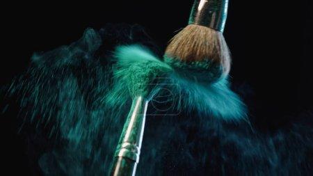 Photo for Cosmetic brushes making splashes of blue powder on black background - Royalty Free Image