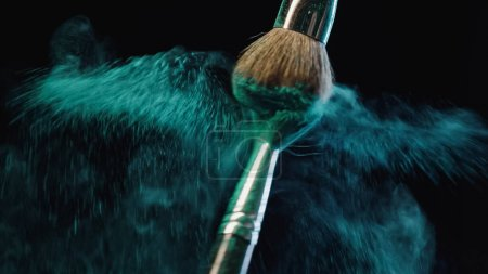 Photo for Two cosmetic brushes making splashes of blue dust on black background - Royalty Free Image
