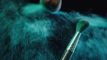 Photo for Soft cosmetic brushes making splashes of turquoise dust on black background - Royalty Free Image