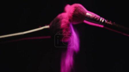 Photo pour Pinceaux cosmétiques flous faisant explosion de poudre rose sur fond noir - image libre de droit