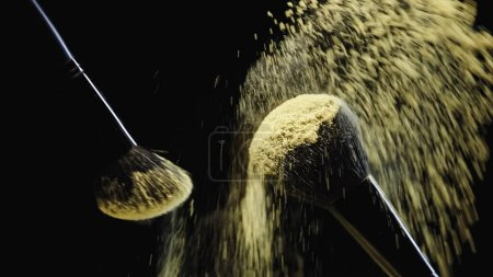 Photo for Cosmetic brushes with yellow powder hitting and making splash of dust on black background - Royalty Free Image