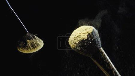 Photo for Cosmetic brushes with yellow holi powder on black background - Royalty Free Image