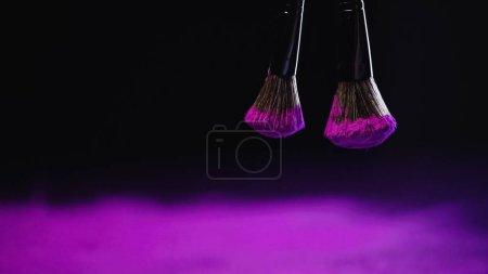 cosmetic brushes with purple holi powder hanging on black background