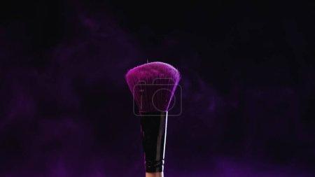 Photo pour Pinceau cosmétique avec poudre de holi violet près de la poussière sur fond noir - image libre de droit