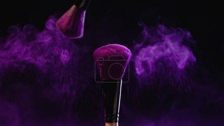 Photo pour Pinceaux cosmétiques avec poudre holi violet près de la poussière sur fond noir - image libre de droit
