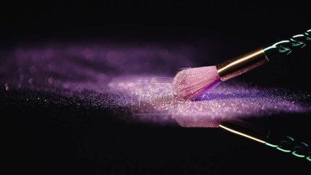 Photo pour Brosse cosmétique douce près de la poussière avec paillettes rose brillant sur noir - image libre de droit