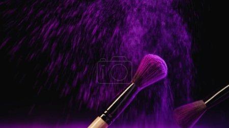 pinceaux cosmétiques avec poudre holi pourpre près des éclaboussures de poussière sur fond noir