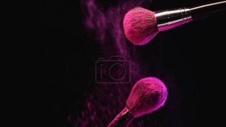 Photo for Cosmetic brushes with bright pink holi powder near dust splashing on black background - Royalty Free Image