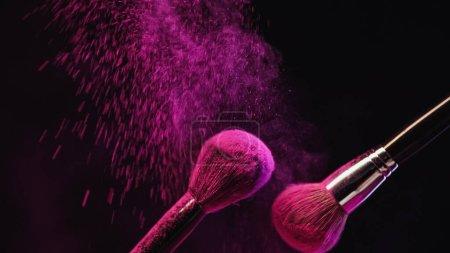 Kosmetikpinsel mit leuchtend rosa Puder auf schwarzem Hintergrund