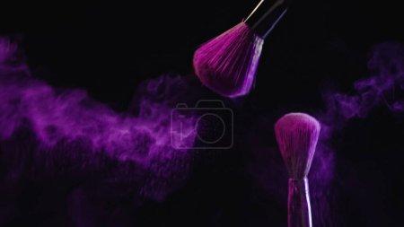 pinceaux cosmétiques avec poudre violette vibrante près des éclaboussures de poussière sur fond noir