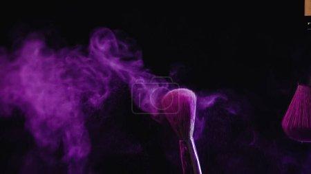Photo for Cosmetic brushes with vibrant purple holi paint near dust splashing on black background - Royalty Free Image