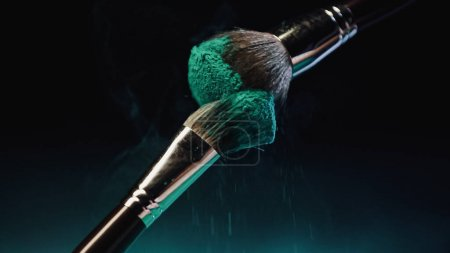 Photo for Cosmetic brushes with vibrant turquoise holi paint near dust on black background - Royalty Free Image