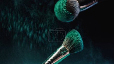 Photo pour Pinceaux cosmétiques avec peinture holi turquoise vif près de poussière éclaboussure sur fond sombre - image libre de droit