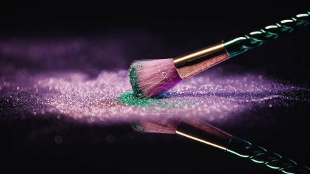 Photo for Cosmetic brush near shiny pink and turquoise dust on black background - Royalty Free Image
