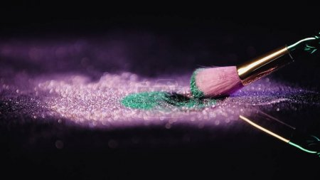 cosmetic brush near pink and turquoise shiny dust on black background