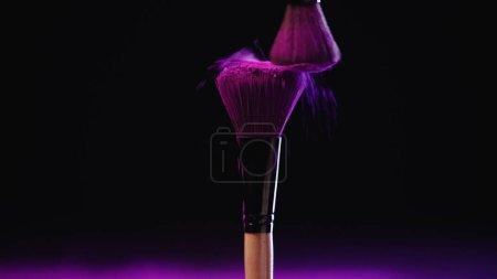Kosmetikpinsel mit rosa Holi-Farbpuder auf schwarzem Hintergrund
