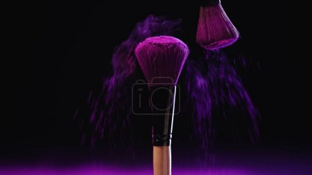 cosmetic brushes with holi paint near pink dust on black background