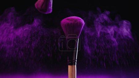 Photo pour Pinceaux cosmétiques doux avec peinture holi près éclaboussure rose de poussière sur fond noir - image libre de droit
