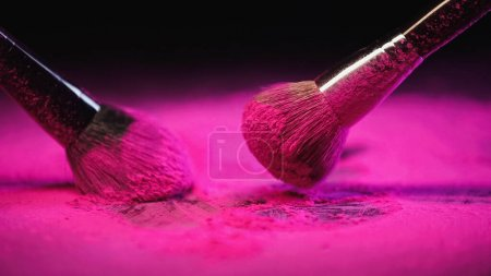 Photo for Messy cosmetic brushes near bright pink powder on black background - Royalty Free Image