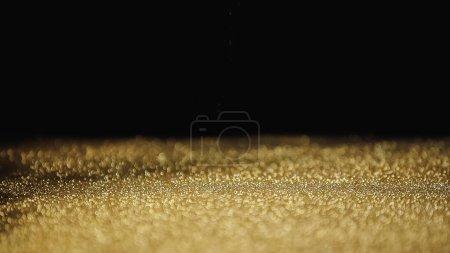 sparkling golden dust with shimmer on black background