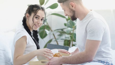 Photo for Bearded man bringing breakfast to cheerful girlfriend with braids in bed - Royalty Free Image