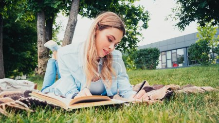 young student writing near book while lying on blanket in park