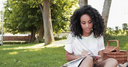 Photo pour Frisé afro-américaine femme écrit dans un cahier dans le parc - image libre de droit
