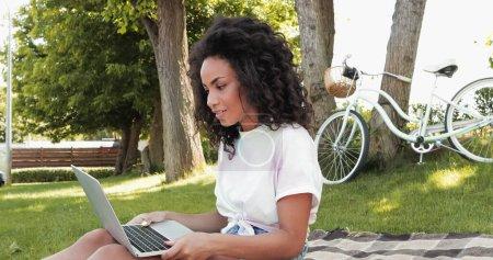 Photo pour Frisé afro-américain pigiste regardant ordinateur portable dans le parc - image libre de droit