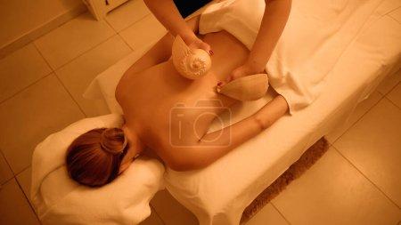 Ansicht von oben professioneller Masseur massiert Rücken einer jungen Frau mit Muscheln im Wellness-Salon
