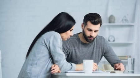 couple discussing finances and looking at calculator on table