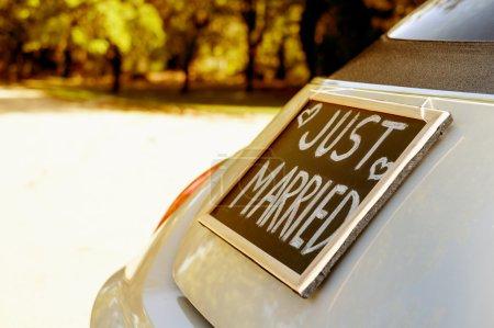 Photo pour Voiture de mariage avec signe juste marié dans un tableau noir - image libre de droit