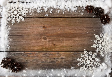 snow frame with snowflakes and cones over wooden background, copy space