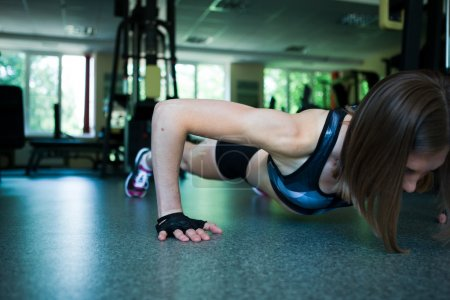 Pretty woman doing push-ups in the gym