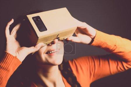 Photo pour Plan couleur d'une jeune femme regardant à travers un carton, un appareil avec lequel on peut faire l'expérience de la réalité virtuelle sur un téléphone portable . - image libre de droit