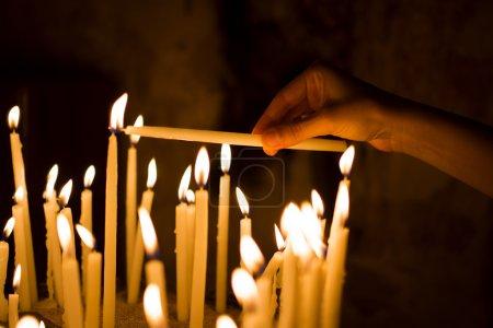 Photo pour Femme allumer des bougies à la main dans une église - image libre de droit