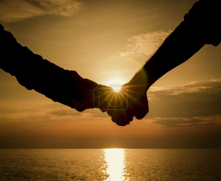 Photo for Silhouettes couples hands on sunset - Royalty Free Image